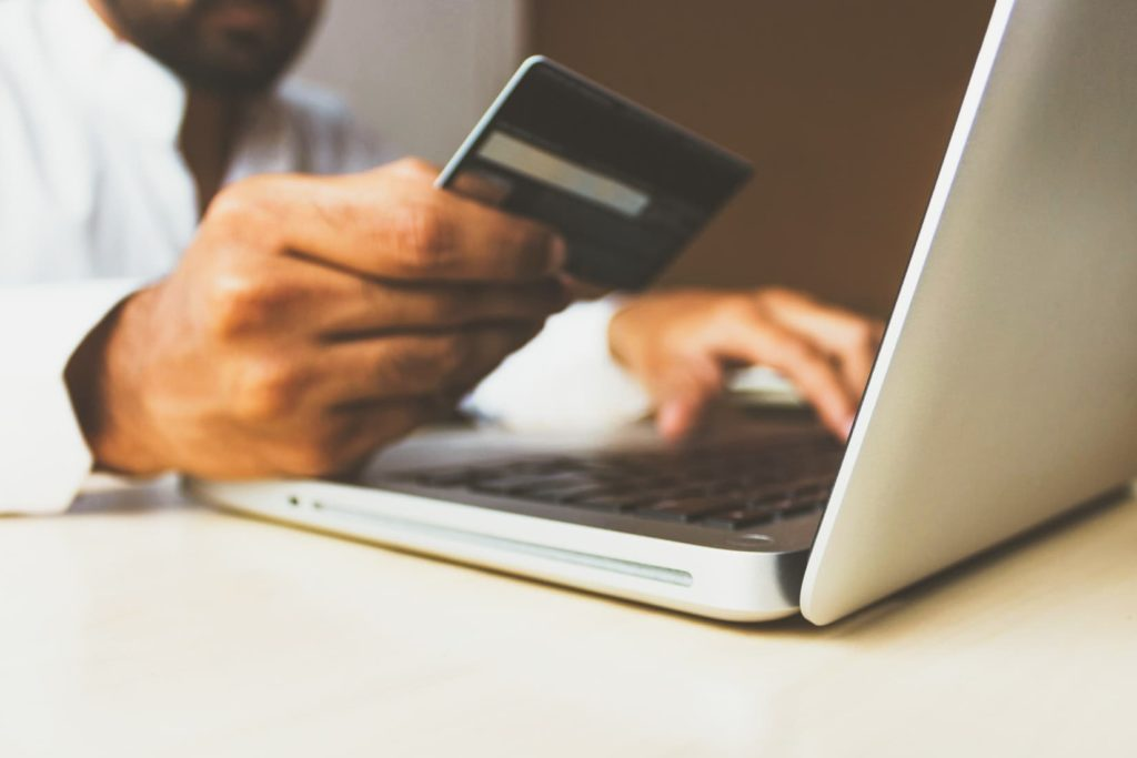 Man using credit card to purchase something on his laptop