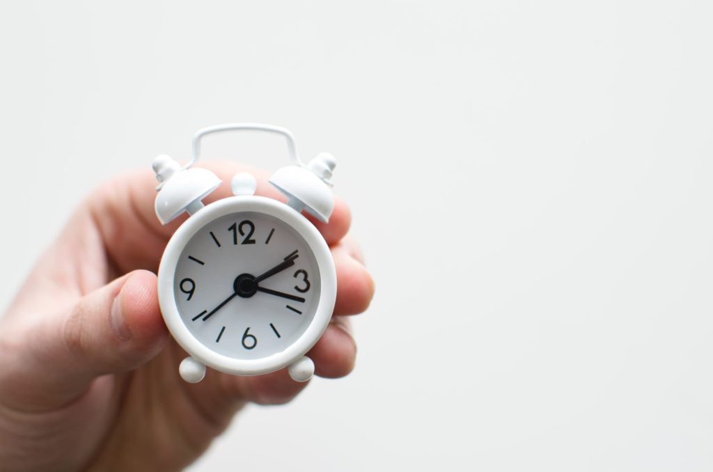Parent's hand holding small white clock to show about time management