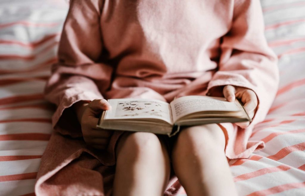 Little girl reading and learning about time management from young